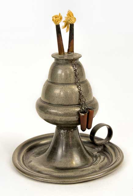 Mid-19 century pewter whale oil lamp with two copper burners with wicks. The lamp has two copper caps on chains to cover the wicks when not in use. The whale oil reservoir is a three-tiered cone mounted on a flaring base with a ring handle.
