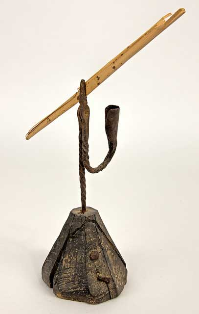 Wrought iron rush light with a twisted shaft. Pincers hold a burning rush. A candle socket wrought from the same piece of iron is attached. Base is crudely shaped piece of wood, now cracked.