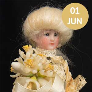 Elaborately dressed Prince Albert doll in white silk and lace, white wig and adorned with flowers tied with a satin ribbon.
