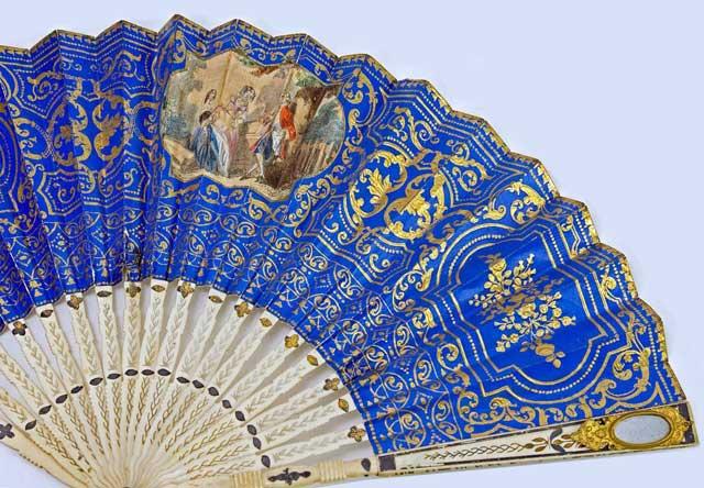 Paper fan with ribs of pierced whale bone. Has discreet mirror on